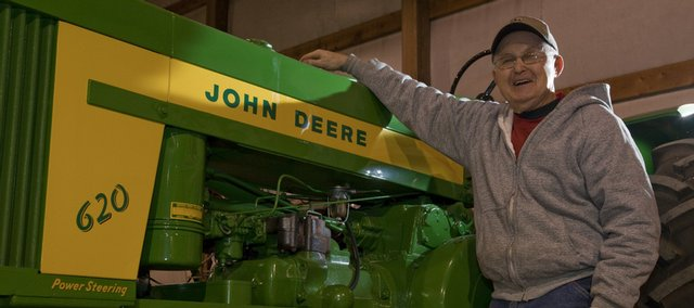 Thurman Duncan, De Soto, likes to take apart old John Deere tractors and restore them. He is standing next to a 1958 Model 620 he found in Eudora.