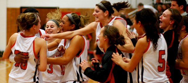 The Lawrence High bench mobs Jordyn Tolefree after her last-second game-winning shot. The Lions beat Olathe East, 63-61, at LHS.