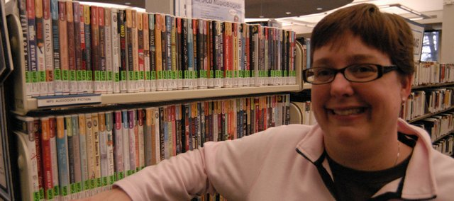 Lynn Koenig, the Lawrence Public Library's adult services coordinator, is shown with the library's collection of audiobooks. In addition to the CD-based collection, the library has greatly expanded its mp3 collection.