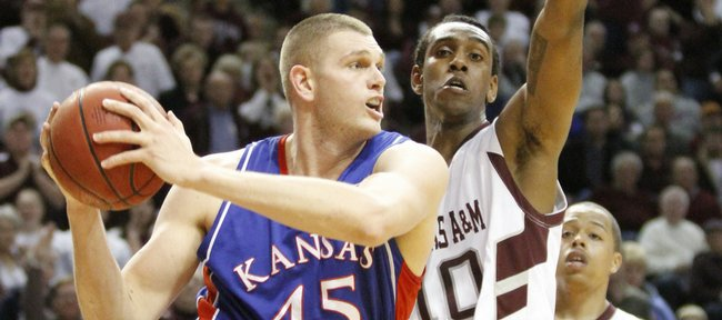 Kansas center Cole Aldrich looks to pass around Texas A&M forward David Loubeau during the first half, Monday, Feb. 15, 2010 at Reed Arena in College Station, Texas.