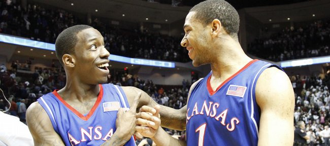 Kansas teammates Tyshawn Taylor (10) and Xavier Henry bump fists as they walk off the court smiling after the Jayhawks' 59-54 win over Texas A&M, Monday, Feb. 15, 2010 at Reed Arena in College Station, Texas.