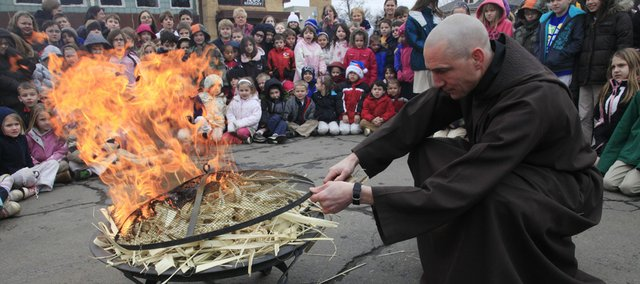 The Rev. John Schmeidler ignites some palm fronds in front of school children from St. John Catholic School, 1208 Ky. The palms, which were used in last year's Palm Sunday services, were burned to make ashes for today's Ash Wednesday services.