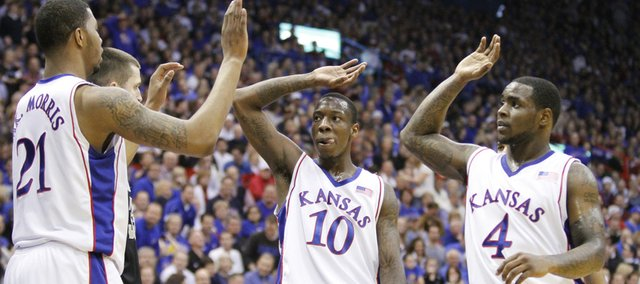 Kansas teammates Tyshawn Taylor (10) and Sherron Collins (4) high-five center Markieff Morris after he got a bucket and a foul from Colorado during the second half, Saturday, Feb. 20, 2010 at Allen Fieldhouse.
