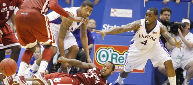 Kansas players Markieff Morris, left, and Sherron Collins defend as Oklahoma guard Tommy Mason-Griffin throws a pass from the floor during the second half, Monday, Feb. 22, 2010 at Allen Fieldhouse.