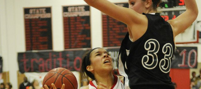 Free State center Ashli Hill (33) contests a shot by Lawrence High's Jasmyn Turner. Hill was a difference-maker on defense, finishing with seven blocks in the Firebirds' 43-40 victory over the Lions on Friday at LHS.