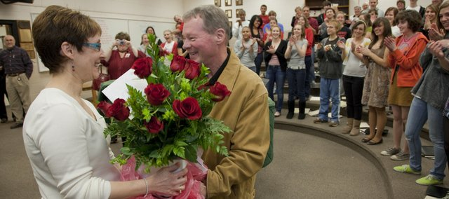 Lawrence High vocal teacher Cathy Crispino, left, is surprised with a dozen roses from her husband, Ron Hathorn, after being named the Lawrence Secondary Teacher of the Year on Monday.