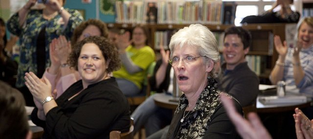 Hillcrest School second-grade teacher Leellyn Tuel wears an expression of disbelief as she is announced as the Lawrence Elementary Teacher of the Year before her colleagues in the school library. Tuel, who has taught in the district for 25 years, received a check for $1,000 from KU Credit Union.