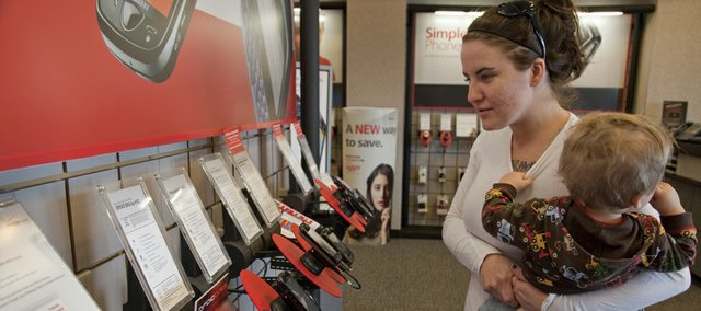 Kristen Sloan of Lenexa looks over a selection of cell phones while shopping at Verizon, 2301 Iowa. While going mobile can come at a hefty price, it doesn't have to break the bank.