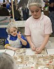 Savannah Moss, 6, left, De Soto, and Catherine Grosdidier, 10, Eudora, right, help package meal bags Saturday for Haiti at Eudora Elementary School. A volunteer group called Numana Inc. organized the Kaw Valley Feeding Haiti event to prepare more than 164,000 meals to ship to Haiti.