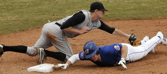Travis Blankenship, bottom, dives back to first base to avoid being picked off during the first game of KU's doubleheader against Iowa Saturday, March 6, 2010.