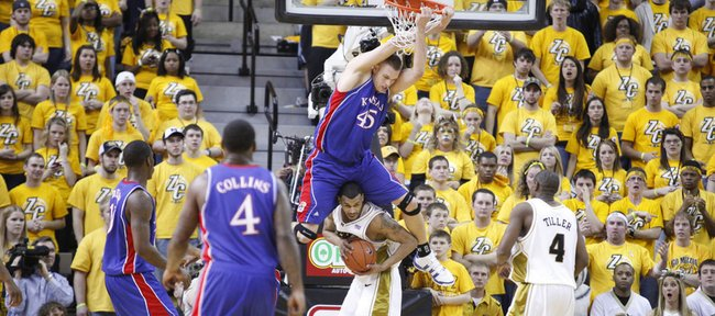 Kansas center Cole Aldrich hangs from the rim over Missouri forward Keith Ramsey after a dunk in the second half, Saturday, March 6, 2010 at Mizzou Arena.