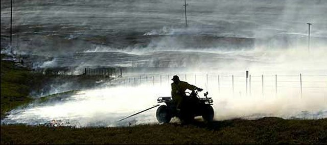 "Todd Peterson drags a ""fire stick"" behind a four-wheeler, dripping kerosene to spread fire, on the Joe Mushrush Ranch near Strong City in this 2004 file photo. Every spring, pastures in the Flint Hills are burned to clear the way for new growth."