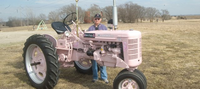 Harold Denholm shows the Farmall tractor that he painted pink in honor of his wife, Aileen, who died of breast cancer.