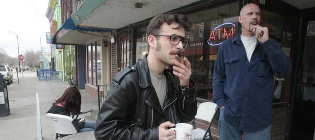 Robert Knapp, Lawrence, left, and David Olcott, Lawrence, smoke Wednesday outside the entrance to Henry's Coffee Shop, 11 E. Eighth St. A statewide smoking ban approved recently will likely make it illegal to smoke in many of the sidewalk dining and drinking areas in downtown Lawrence.