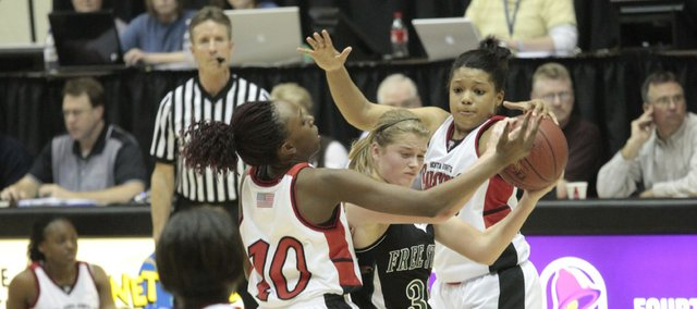 Free State's Chelsea Casady, (32) is swarmed by Wichita Heights defenders Wednesday, March 10, 2010, at Emporia during the first-round game loss against Wichita Heights in the girls Class 6A state championships.