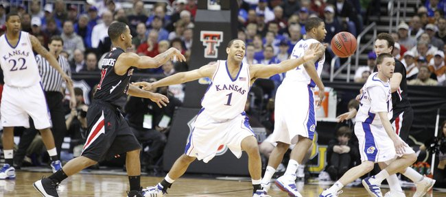 Kansas forward Xavier Henry extends as Texas Tech guard John Roberson passes to the wing during the second half Thursday at the Sprint Center in Kansas City, Mo.