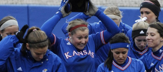 Mariah Montgomery, center, is surrounded by her teammates after hitting a two-run home run in a game against Valparaiso in the home opener for KU at KU's Arrocha Ballpark, Thursday, March 11, 2010.