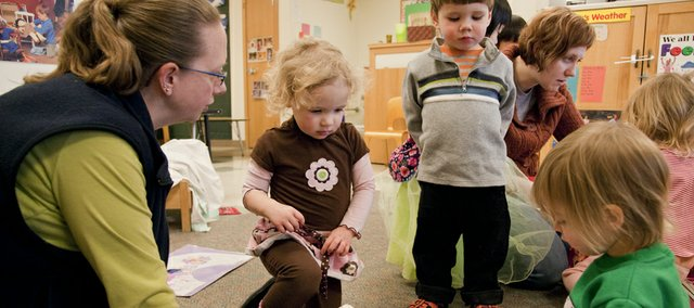 Lia Handy, a teacher at Hilltop Child Development Center, encourages Madilynn Prewitt, left, and Anders Benson to wait for Allison Gleason to finish playing with a toy phone at Hilltop Child Development Center. Teaching children to share toys is one way to head off a biting situation.