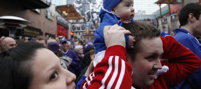 Kansas City, Kan. residents Raquel and Steven Bayless watch the excitement of the Jayhawks' pregame pep rally with their six-month-old daughter Alexis prior to tipoff against Kansas State on Saturday in Kansas City, Mo.