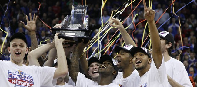 Confetti pours over the Kansas Jayhawks as they hoist the Big 12 Tournament trophy after defeating Kansas State 72-64 Saturday in Kansas City, Mo.