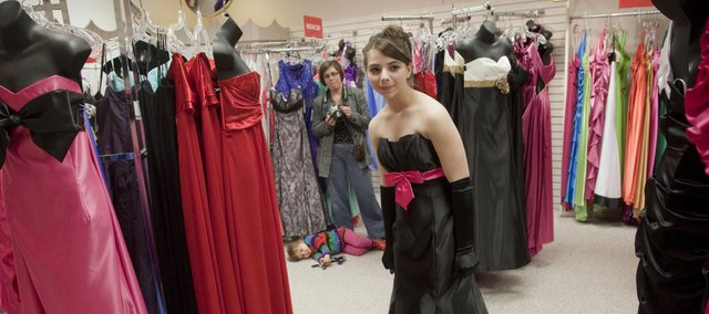 Kattia Andrews, a junior at Marmaton Valley High School near Moran, tries on a prom dress Saturday at Weaver's, 901 Mass. Shopping with Andrews in background at left is her sister Sonia Jones, Garnett, and Jones' daughter Sophia, 2.