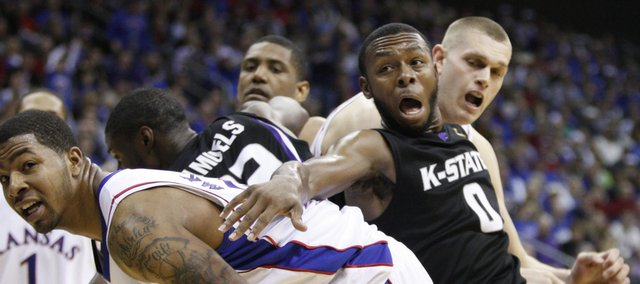 Kansas forward Markieff Morris, left, and center Cole Aldrich get physical with Kansas State guard Jacob Pullen going for a rebound during the second half Saturday in Kansas City, Mo.