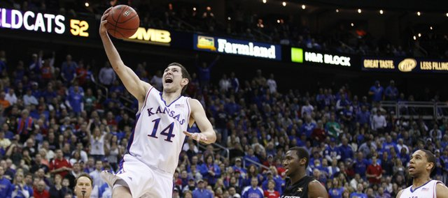 Kansas guard Tyrel Reed elevates to the bucket past Kansas State forward Curtis Kelly and teammate Xavier Henry during the second half Saturday in Kansas City, Mo.