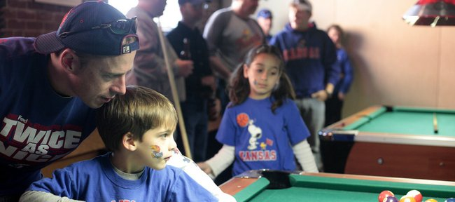 Mike Dalke, Dallas, helps his son Ben, 5, line up a pool shot at the Bricktown Brewery during a Kansas Alumni gathering before KU's game Thursday March 18, 2010. Dalke is a 1991 KU graduate. His daugher Madeline, 8, is in the background at center.