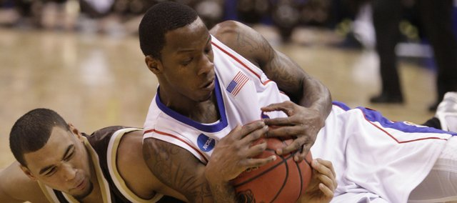Kansas guard Tyshawn Taylor wrestles for a loose ball with Lehigh guard Marquis Hall during the first half, Thursday, March 18, 2010 at the Ford Center in Oklahoma City.