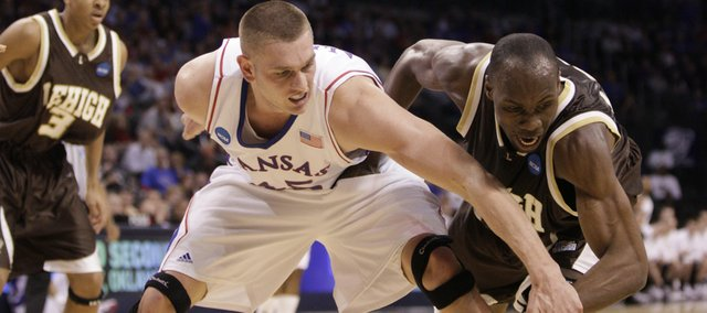 Kansas center Cole Aldrich and Lehigh forward Zahir Carrington compete for a loose ball during the first half, Thursday, March 18, 2010 at the Ford Center in Oklahoma City.
