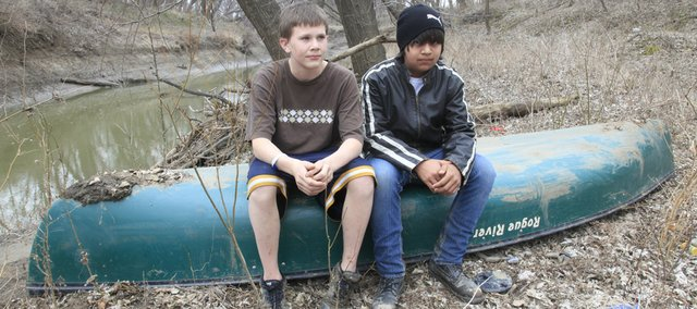 On Friday, Nick Board, 14, left, and J.R. Quaempts, 14, both of Eudora, find the canoe that they had been taking along the Wakarusa River from Clinton Lake to Eudora. As they were paddling down the river Thursday evening, they became stranded until emergency personnel found them around midnight.