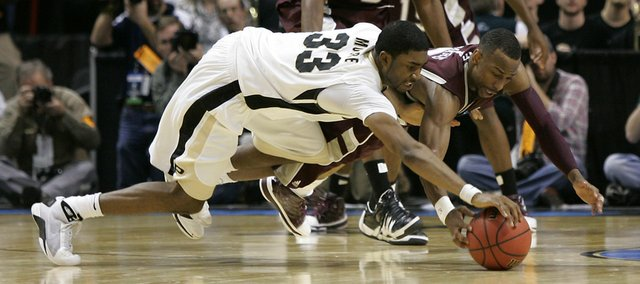 Purdue's E'Twaun Moore (33) and Texas A&M's Dash Harris dive for a loose ball as Texas A&M's Bryan Davis looks on at top in the final seconds of the second half of an NCAA second-round college basketball game in Spokane, Wash., Sunday, March 21, 2010. Purdue beat Texas A&M 63-61 in overtime.