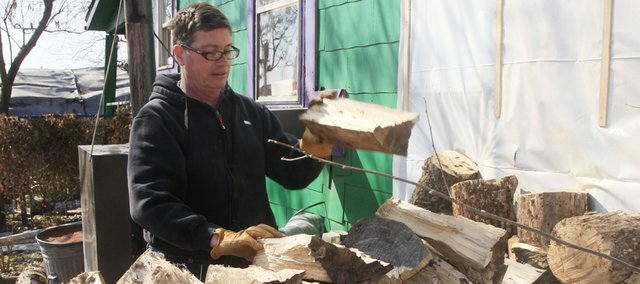 """Mike Garrett, 55, stacks firewood on his property at 1563 U.S. Highway 40. He heats a small home northeast of Lawrence entirely with wood. He says he likes the exercise. """"It is kind of cool to feel the ground shake when you bring a big oak tree down,"""" he says."""