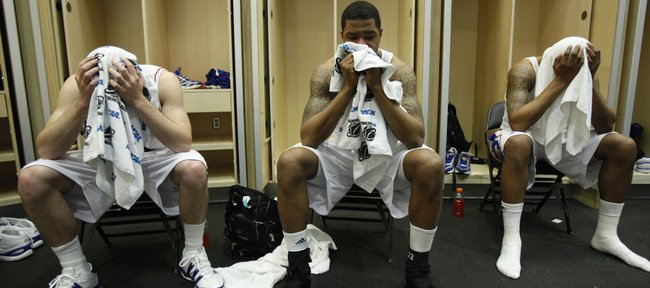 From left, Kansas players Tyrel Reed, Marcus Morris and Markieff Morris hold back tears in their towels in the Jayhawks' locker room following their 69-67 loss to Northern Iowa, Saturday, March 20, 2010 at the Ford Center in Oklahoma City.