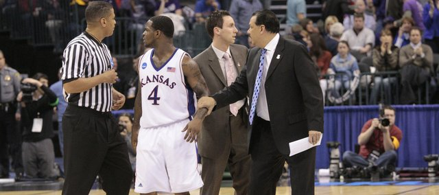 Sherron Collins speaks with the referee at the end of the first-half as he and assistant coaches Brett Ballard and Kurtis Townsend leave the court, trailing the University of Northern Iowa Saturday, March 20, 2010, in Oklahoma City, OK.