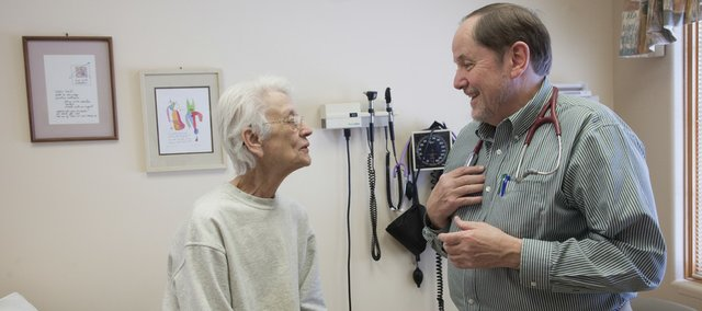 "Dr. Steven Bruner, of Lawrence Family Medicine & Obstetrics, confers Monday with patient Carol Glover. Bruner says he's happy that the health care reform bill has passed. ""I am very thankful that there are some politicians who actually have a little bit of courage to see this through really hard times."""