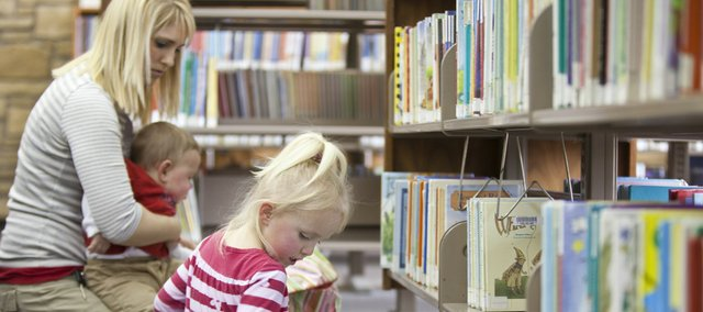 Ryann Newkirk, 3, chooses from a selection of books she has pulled from the shelves as she, her mother, Nealy Newkirk, and 8-month-old brother Nicholas visit the children's room of the Lawrence Public Library on Tuesday. Library officials have requested that the city put a library expansion project on the November ballot. Among the areas included within the expansion and renovation plans are the children's room, the computer area and public meeting rooms.