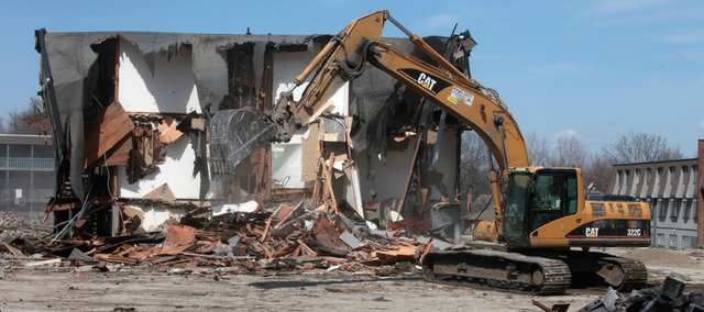 Workmen for King's Construction of Oskaloosa demolish the former Boardwalk Apartments complex Thursday at 524 Frontier Road. All nine of the 1960s-era buildings will come down to make way for a $10 million apartment project.