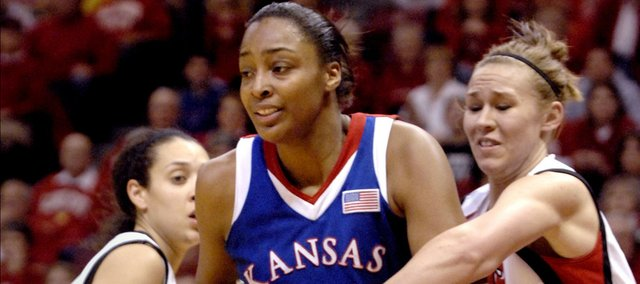 Kansas' Carolyn Davis turns away as Illinois State's Katie Broadway reaches for the ball Thursday, March 25, 2010, during the second half of a Women's NIT game at Redbird Arena in Normal.