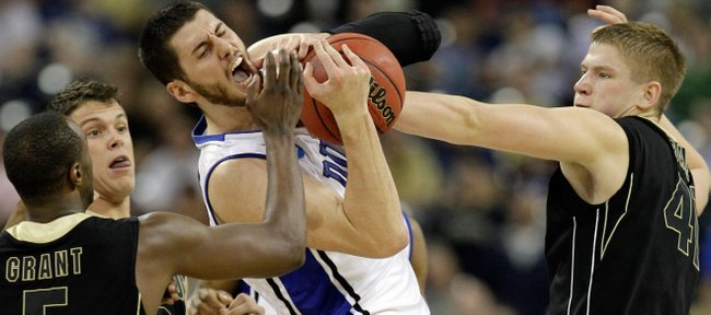 Duke's Brian Zoubek battles for a rebound against Purdue's Keaton Grant (5), Chris Kramer and Patrick Bade, right, during the first half of an NCAA South Regional semifinal college basketball game in Houston, Friday, March 26, 2010.