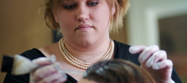 Micki Colgan of Headmasters Salon, 809 Vt., colors the hair of client Nancy Riding, Shawnee. Colgan, the salon co-owner, says she's seeing clients spread out their coloring appointments to save money.