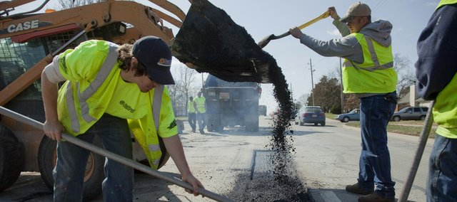 After a long, cold winter, the city is now left to deal with many streets with potholes and damage from freezing weather. Crews from Sunflower Paving Inc., Lawrence, repair and repave sections of the westbound lane of Sixth Street near Eldridge Road on Thursday.