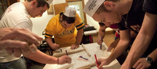 Alpha Epsilon Pi fraternity members Michael Solganik, Overland Park junior, left; Brett Samet, San Antonio sophomore, and Steven Meyer, Omaha, Neb., sophomore, work to perforate rolled pieces of matzah at the fraternity. Members of the fraternity spent an evening with Rabbi Zalman Tiechtel of the Chabad Jewish Center learning about the traditions of Passover as well as how to prepare matzah, a traditional Passover food.