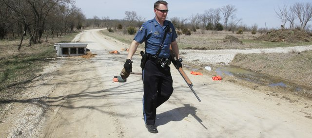 Kansas Highway Patrol trooper J.D. MacEwan carries a shotgun from a pile of items discarded during a high-speed chase that ended in western Douglas County.