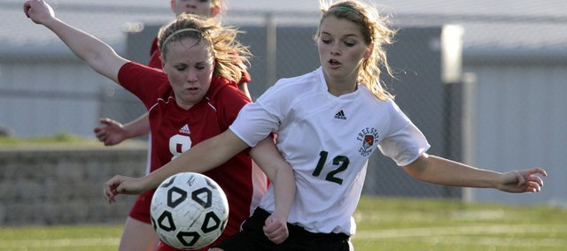 Freshman forward Abby Casady (12) fights for the ball against Briana Caspers in fist half action Tuesday, March 30, 2010 as Free State hosted Shawnee Heights girls soccer. The teams ended the game tied after two overtime periods.