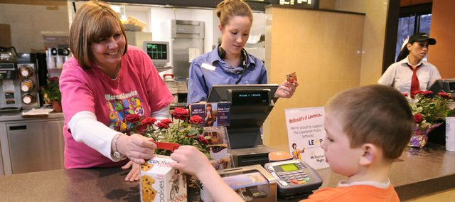 Hillcrest School principal Tammy Becker hands off a box of cookies to Hillcrest second-grader Kristian Hall for McTeacher Night at McDonald's, 1309 W. Sixth St., in this March 2009 file photo. Marilyn and Tom Dobski operate several restaurant franchises around Kansas, including McDonald's.