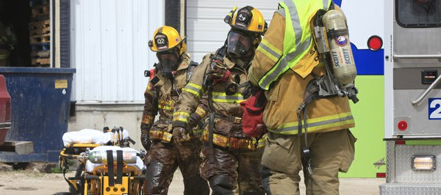 Lawrence firefighters exit MagnaGro International at 600 E. 22nd covered with a purplish liquid. Emergency crews responded to the scene of a fatal industrial accident Thursday afternoon.