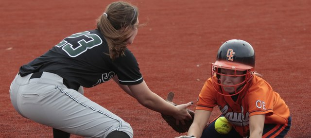 Free States Elizabeth Hazlett attempts to dig the ball out of the dirt to tag out an Olathe East runner at first base. The Firebirds lost, 14-1 and 3-1, Thursday at Free State High.