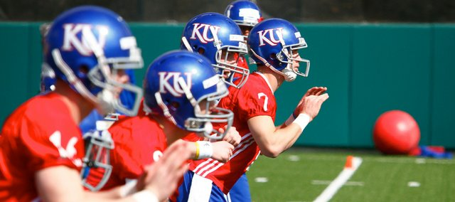 The quarterback candidates for Kansas University run through a drill at spring practice last Sunday. It's too early to tell who is leading the race to replace Todd Reesing.