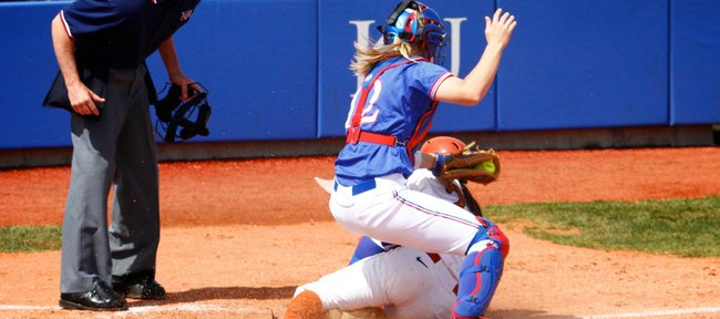 A Texas baserunner slides in safely to home under the legs of KU catcher Brittany Hile during the game on Saturday, April 3, 2010. The Longhorns beat the Jayhawks 6-2.